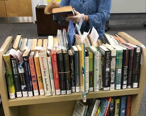 Yadkin County Branch Librarian cleans returned books to be reshelved.