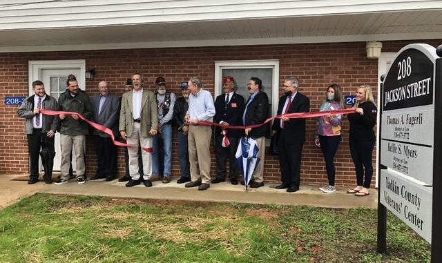 Veterans and county officials gather for a ribbon cutting ceremony for a new Veterans' Center office in downtown Yadkinville.