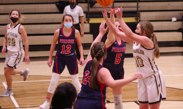 Alexis Ball (12), Brittney Gammons (5), and Hailey Workman (24) defend the ball.