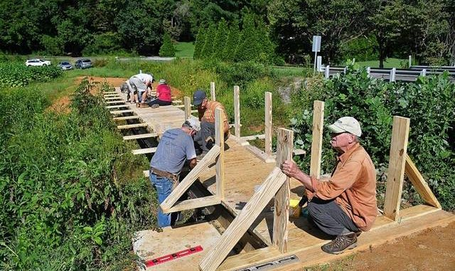 Elkin Valley Trails Association volunteers build a bridge over Grassy Creek on the Mountains-To-Sea Trail in October 2020. The EVTA is celebrating its 10-year anniversary.                                  Courtesy EVTA