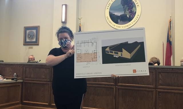 Jonesville Librarian Jennifer Rogers shows of the design plan for the proposed expansion of the library building which is located on N. Swaim St.