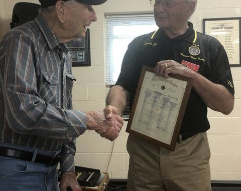 American Legion Post 336 Commander David Shore shakes hands with Clyde Wall, a 70-year member of the American Legion.