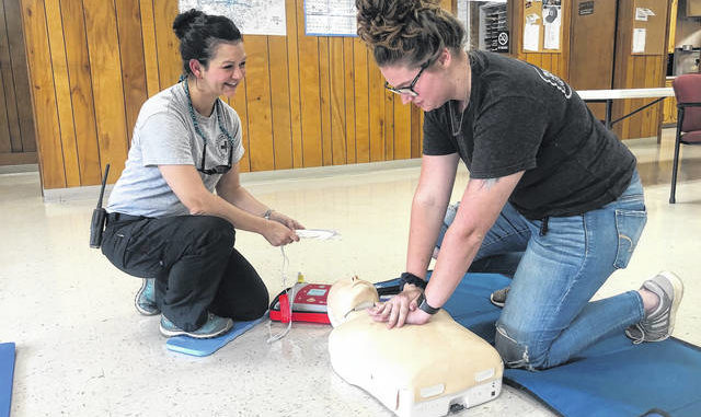 Members of the Yadkin County Rescue Squad Julie Zebron and Zoey Staley demonstrate CPR and the use of an AED.
